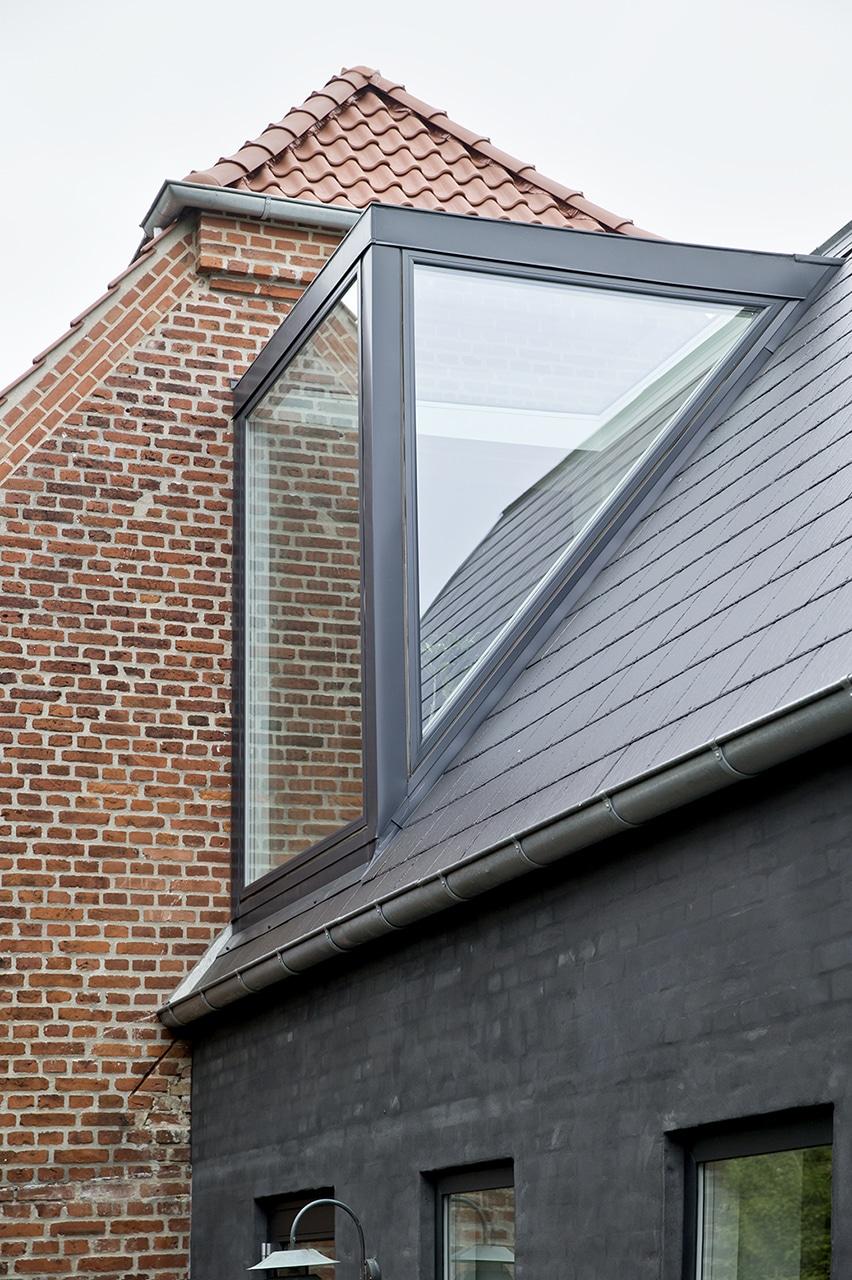Tilbygningen er pudset op med sort indfarvet puds med et dertil matchende mørkt tag.