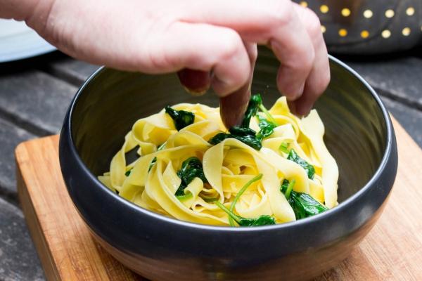 Voeg de champignons en de fijngehakte walnoten toe bij de pasta