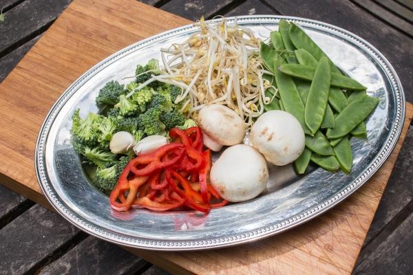 Snij de kippenfilet in reepjes, de champignons in blokjes, de puntpaprika in ringen, de roosjes van de broccoli en de knoflook fijn