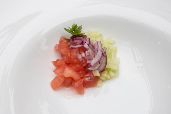Serveer in een diep bord 3 kleine hoopjes van de fijngesneden stukjes tomaat, komkommer en rode ajuin. Werk af met enkele blaadjes basilicum