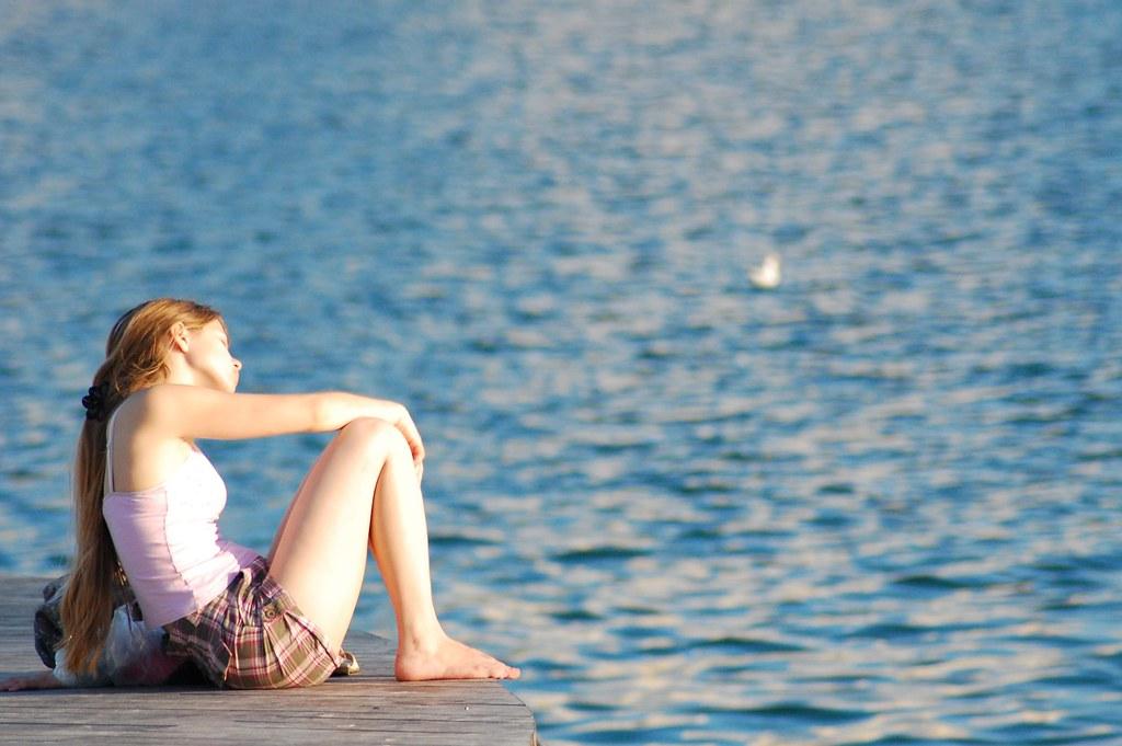Image of teenager sitting near a lake