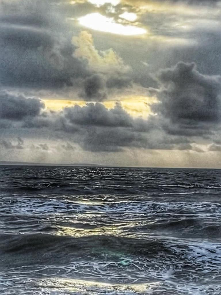 A tranquil sea with a chink of sunlight peeping through the clouds.