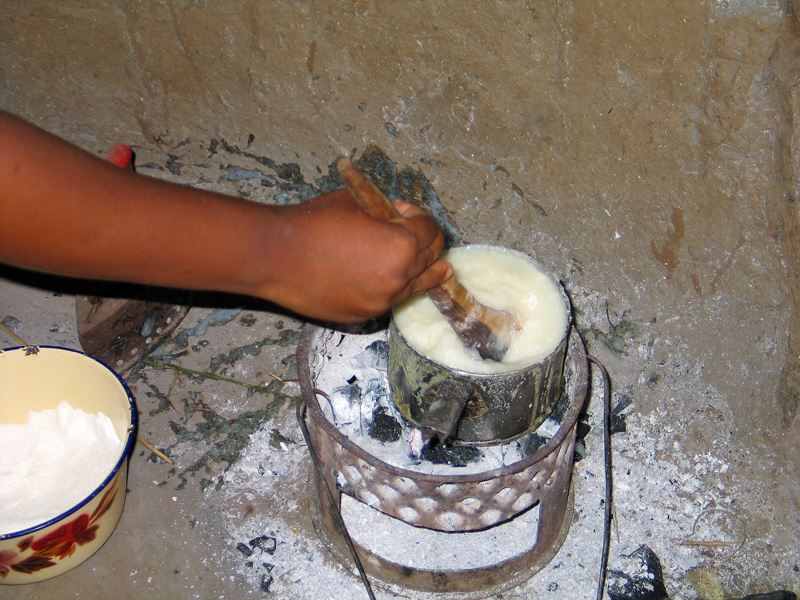 Cooking Nshima over charcoal fire