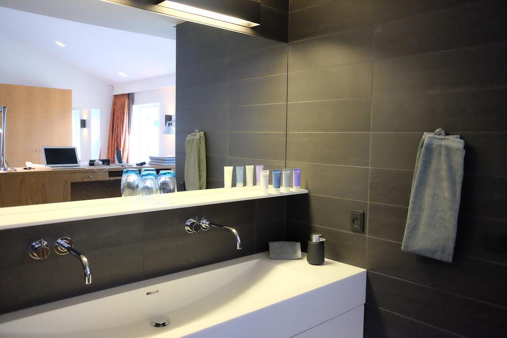 Håndvask til tandbørstning for to ligger i åben forbindelse med rummet - WC og styrtebad på hver sin side og i separate rum