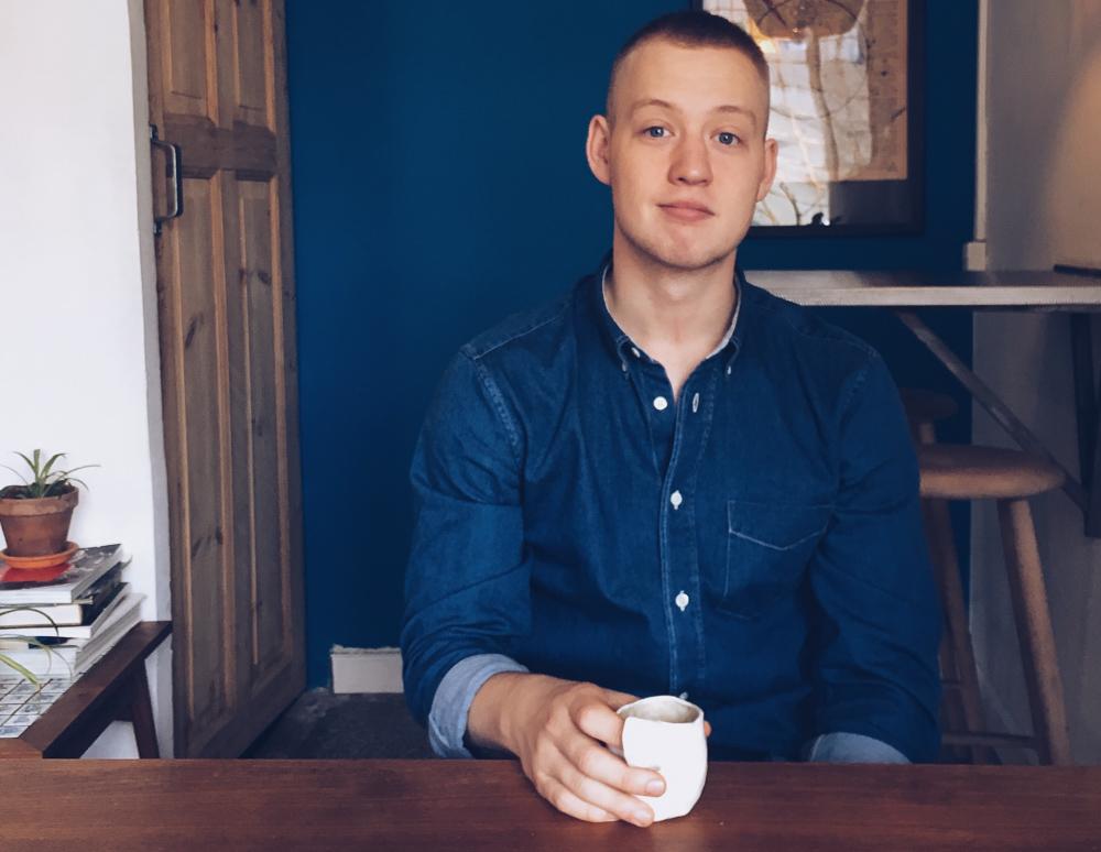 Jeppe H - med denim og matchende baggrund samt kaffekop.