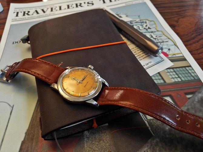 Læder med læder på. Og ur. Omslaget bliver patineret med tiden - sådan er det heldigvis med læder.