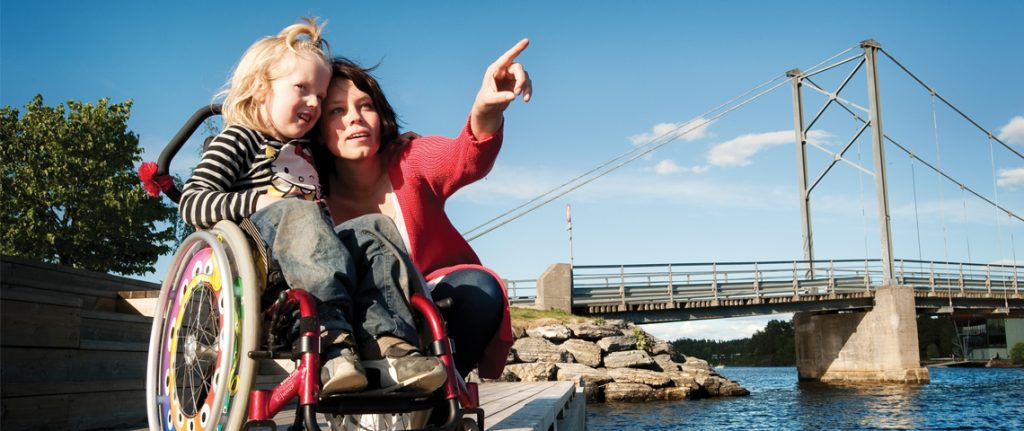A mother with her daughter in a wheelchair.