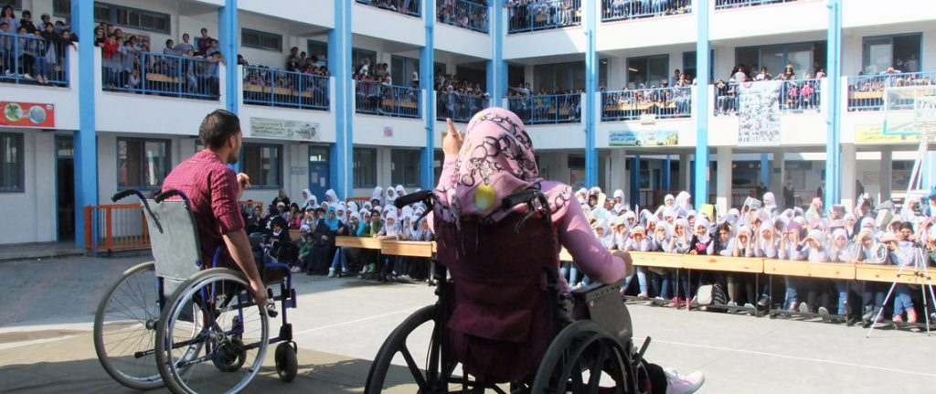 A man and a woman, both in a wheelchair, are on a stage in front of many school children.