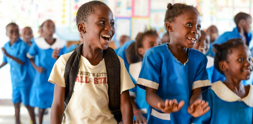 School children in a classroom are looking excited.
