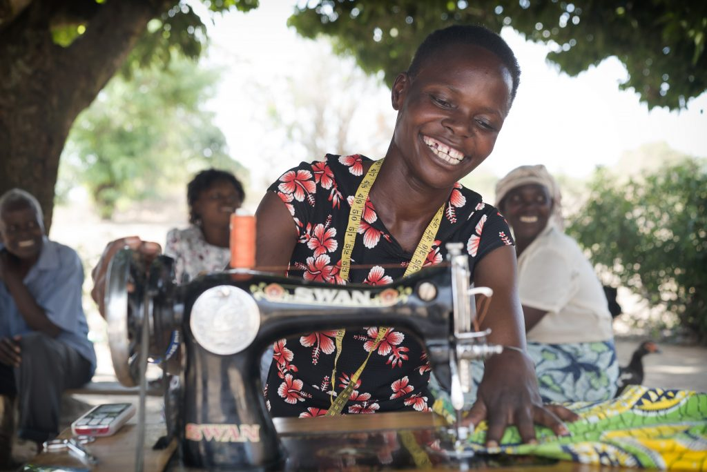 A woman is working on a sewing machine and smiling.