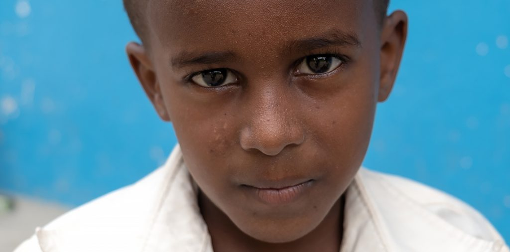 A young boy looking into the camera.