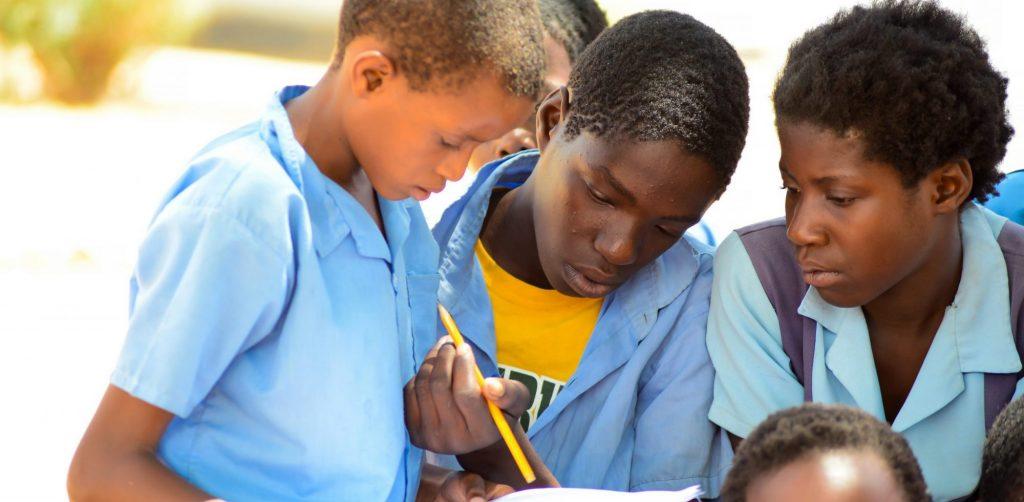 Three schoolchildren reading a sheet together.