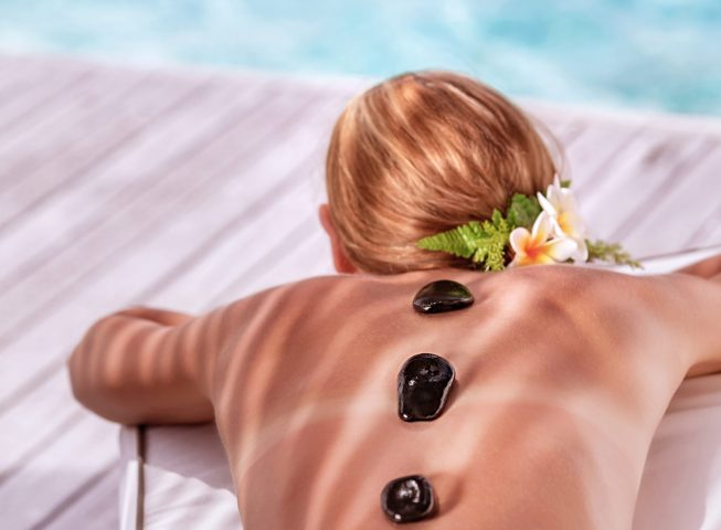 Hot stone massage on luxury spa resort on the beach, young beautiful woman lying down outdoors and enjoying dayspa, summer vacation concept