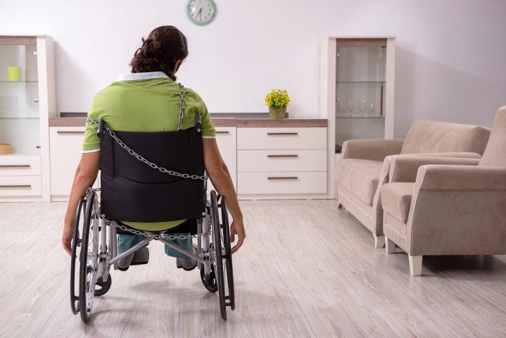 Mann i rullestol sitter alene i et rom med ryggen til. Ser trist ut.