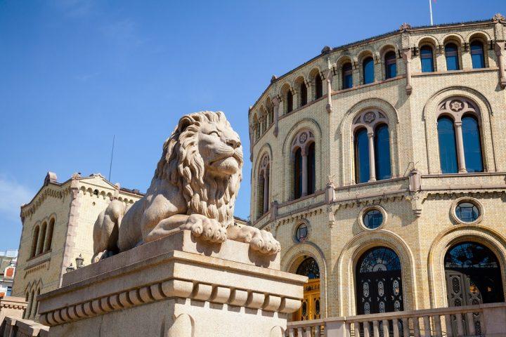 Bilde av Løvestatuen utenfor Stortinget med stortingsbygget i bakgrunnen
