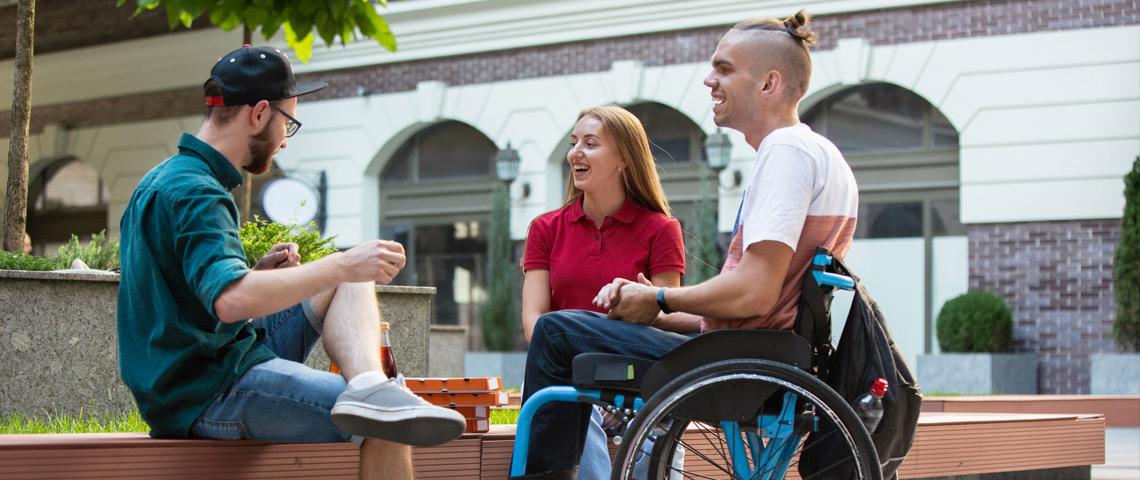 Tre unge mennesker sitter på en benk og snakker sammen smilende. En er i rullestol