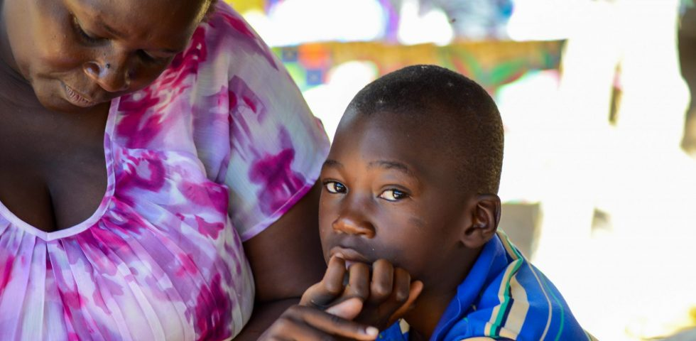 En ung gutt sitter med moren sin.