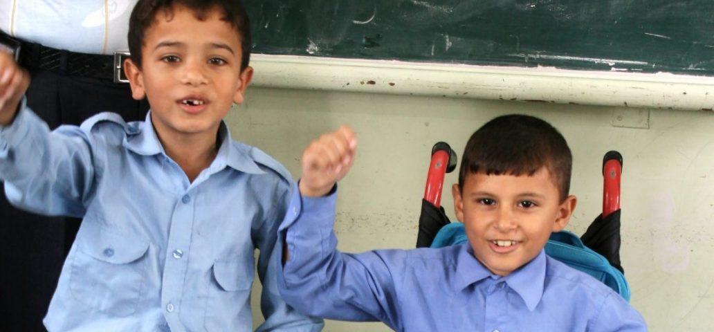 To unge gutter, en av dem sitter i en rullestol.