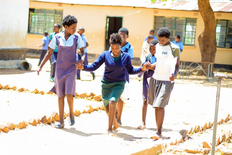 Tre barn går hånd i hånd i skolegården.