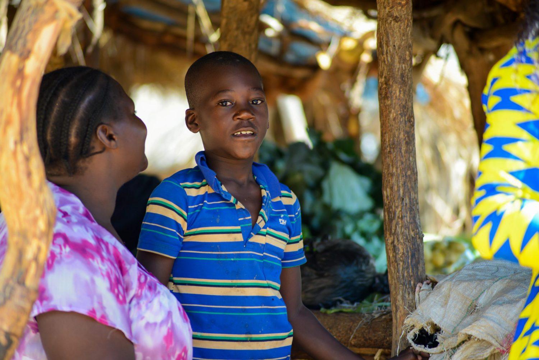 En ung gutt står ved siden av moren sin.