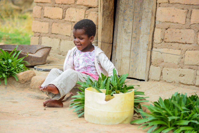 En liten jente sitter foran et hus.
