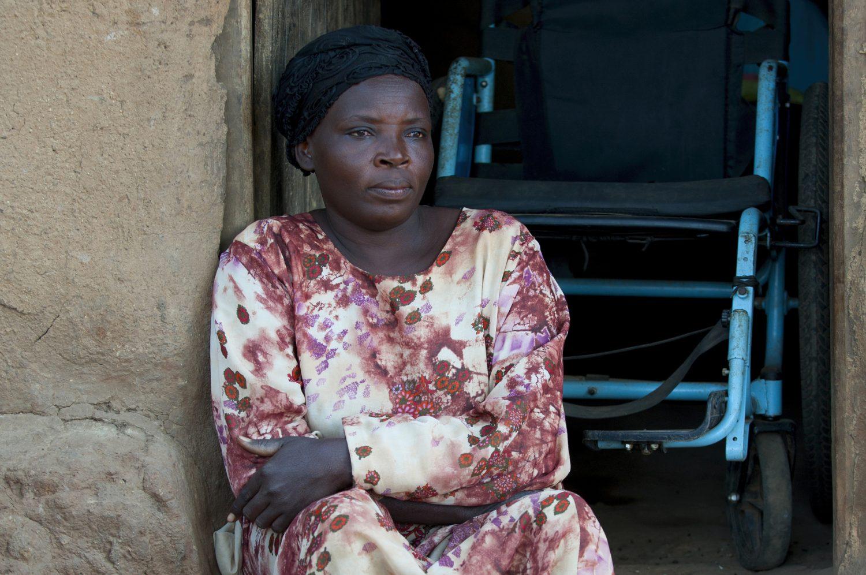 En kvinne sitter i døråpningen, med en rullestol bak seg.