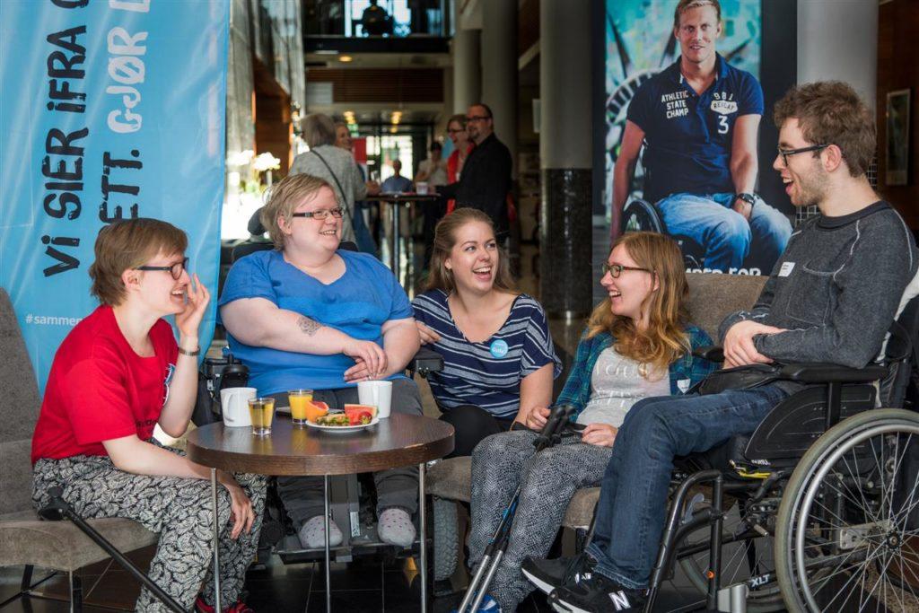 Unge mennesker samlet rundt et bord smiler.