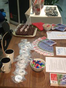 Standbord med kake, reflekser, brosjyrer og kopper