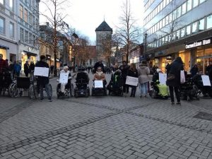 Mange personer med plakater, de fleste i rullestol, sperrer av en gågate