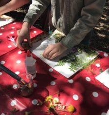 Enfant qui colle des éléments naturels sur une feuille