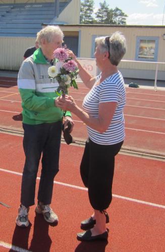 Berith Karlsson överlämnar en blomsterkvast till Carl-Erik