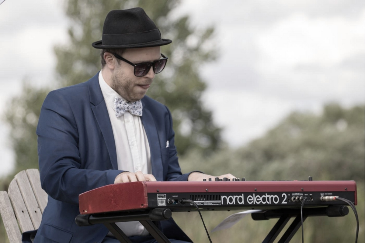 Oscar Gilbert spiller klaver i blåt jakkesæt