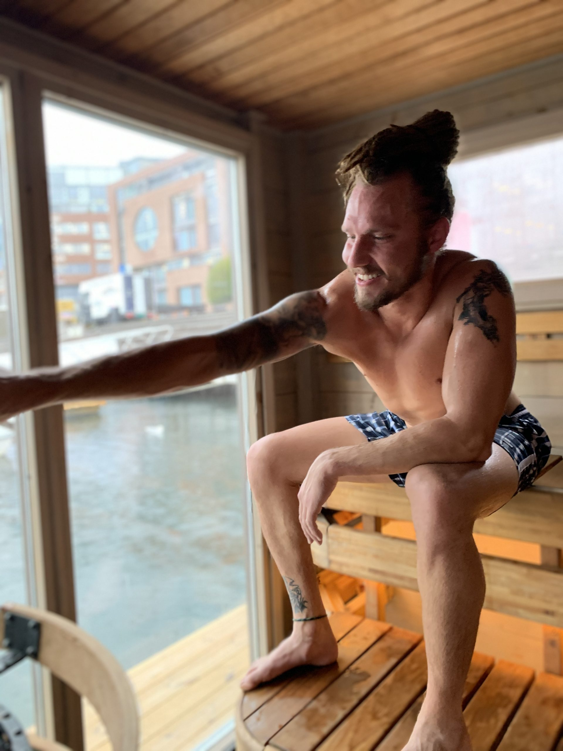 man pouring water in the sauna