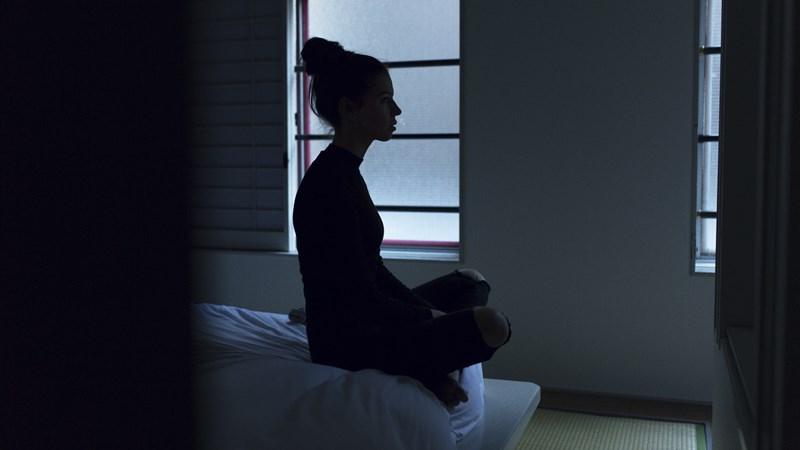 Insomnia, dame som sitter på sengekanten i mørkt rom