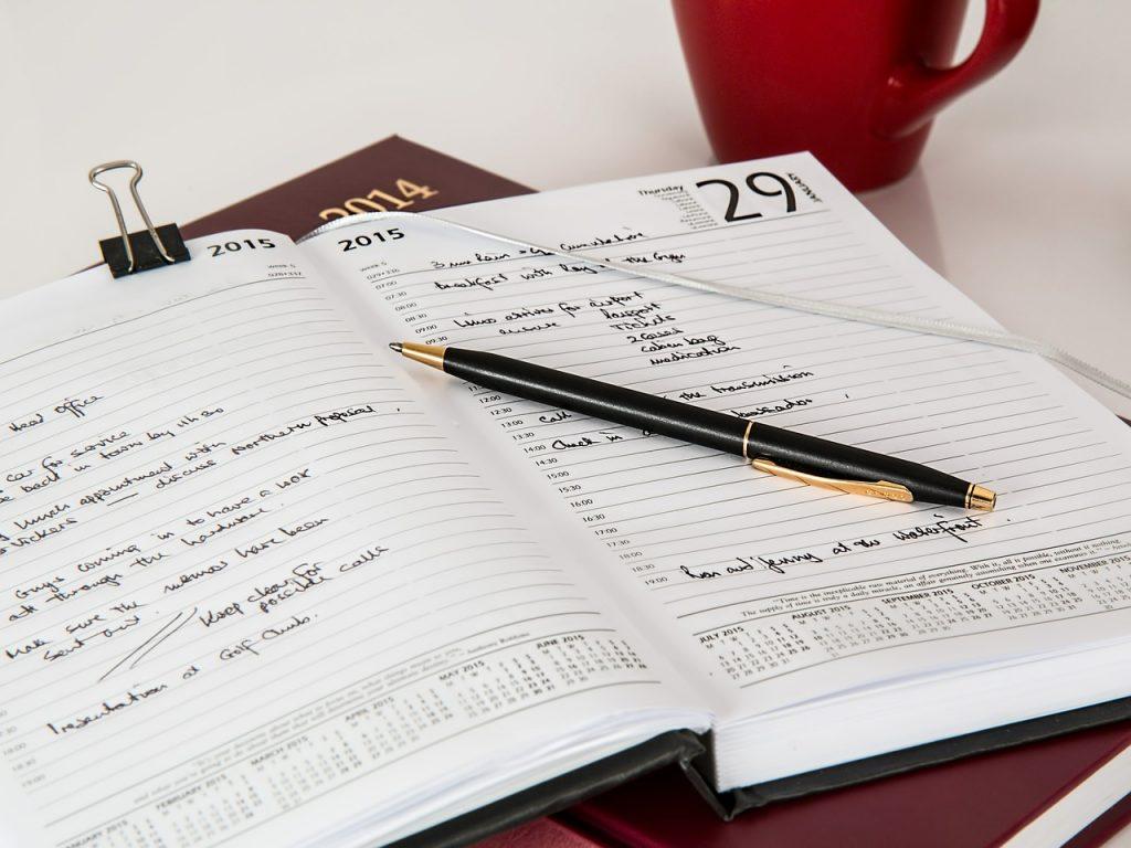 en uppslagen kalender med penna på