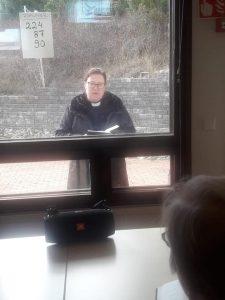 präst står utanför fönstret och sjunger