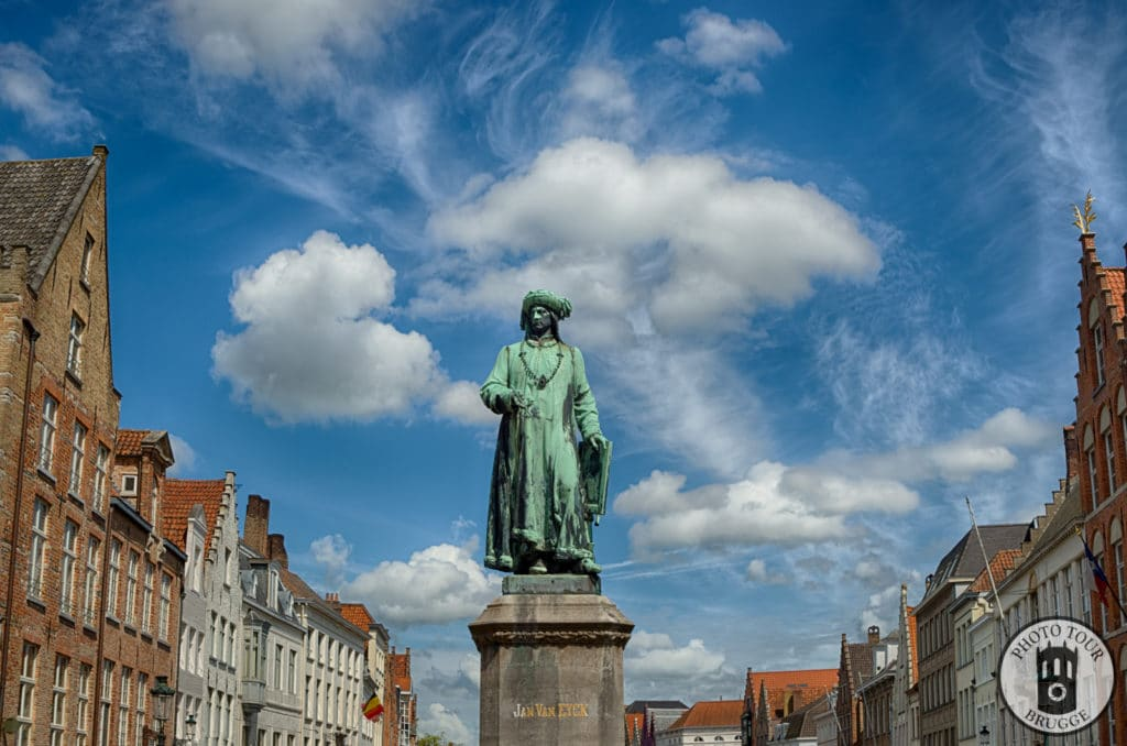 The statue of Flemish painter Jan Van Eyck standing at the former shipping port of Bruges Belgium. Photo by Photo Tour Brugge.