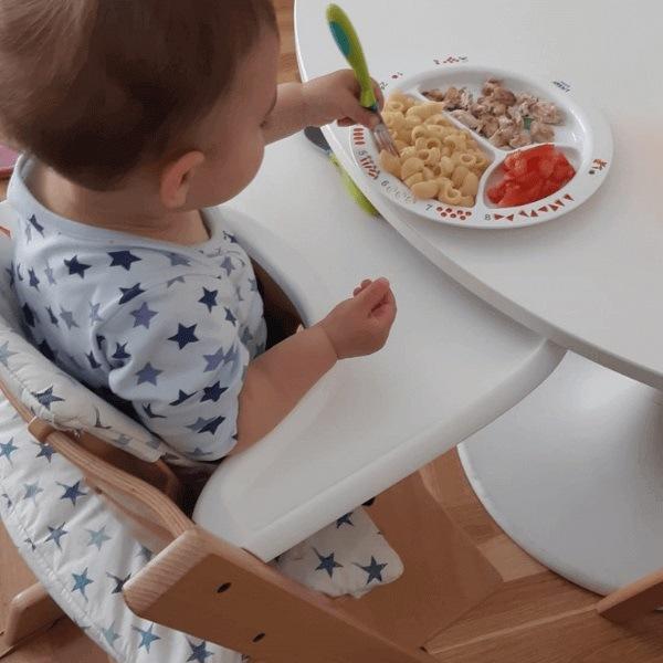 Bebé comiendo en trona Stokke