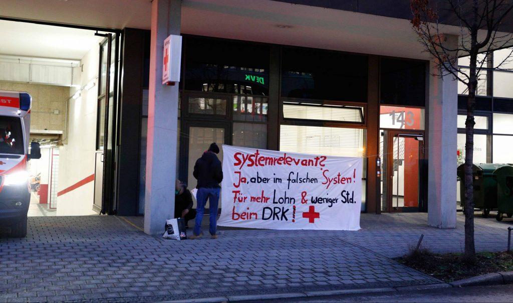 """Transparent mit der Aufrschrift """"Systemrelevant? Ja, aber im falschen System! Für mehr Lohn und weniger Stunden beim DRK"""" vor einer Rettungswache"""
