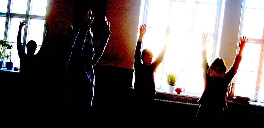 flera personer sträcker armarna i luften då de utövar Kum Nye yoga i Göteborg