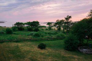 Kväll vid Solvik med trädgård och havsvik i vackert ljus.