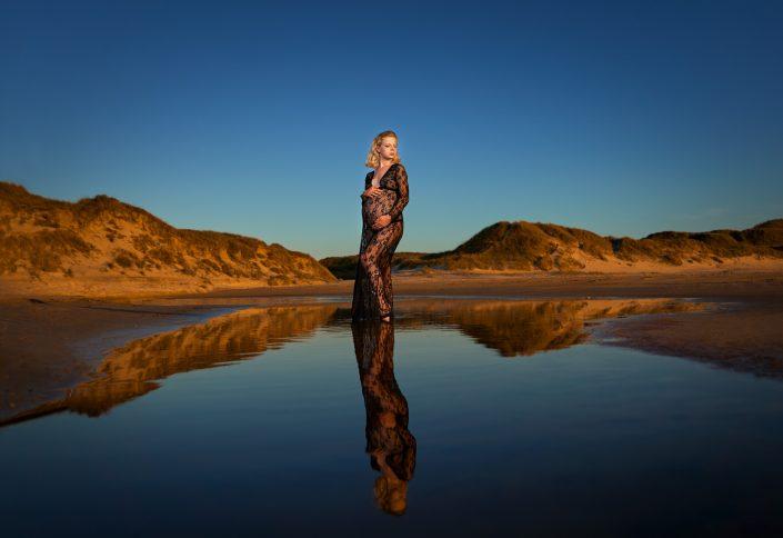 gravid-kvinde-står-strand-vannkant-speiling-sort-blonde-kjole-holder-mage