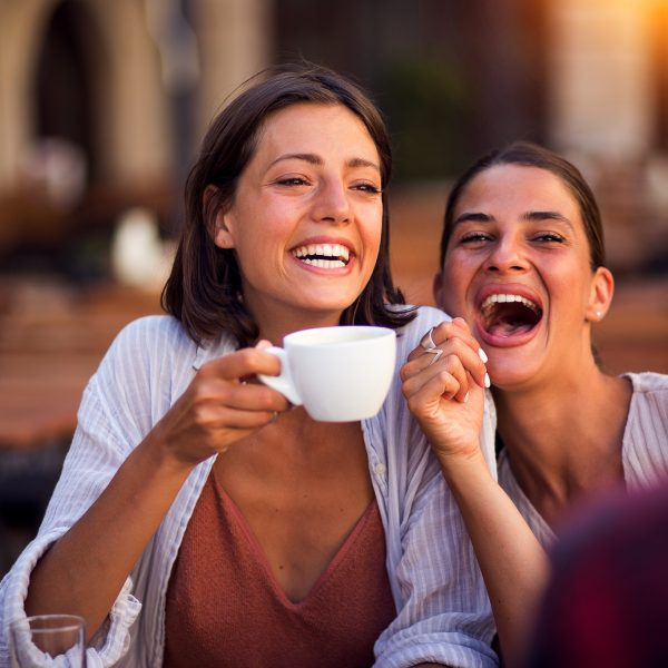 Smiling friends drinking coffee and laughing