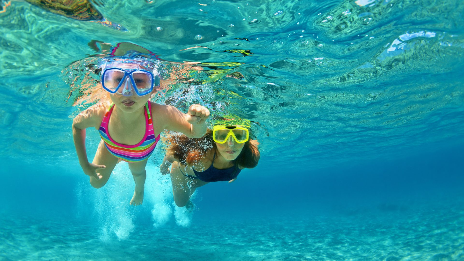 Happy family - mother with baby girl dive underwater with fun in sea pool. Healthy lifestyle, active parent, people water sport outdoor adventure, swimming lessons on beach summer holidays with child