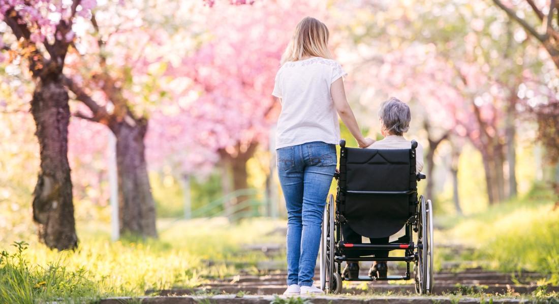 Ældre kvide i kørestol med pårørende
