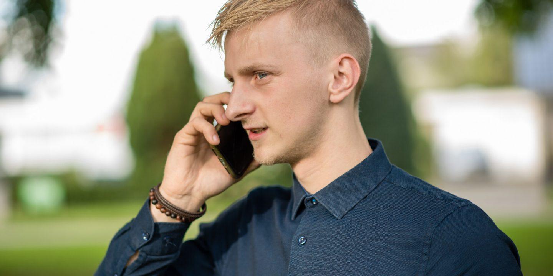 Gratis bedrijfsfotografie op maat, Jonge man buiten aan het bellen met een klant.