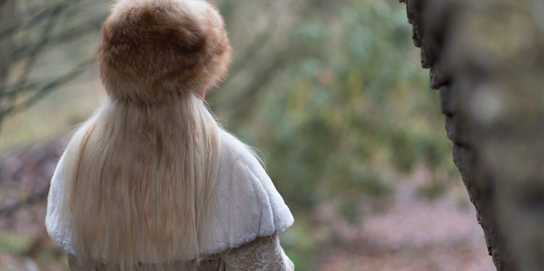 Vrouw met kraag en bontmuts staart in het bos, van achteren gezien