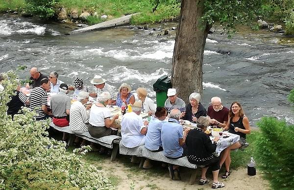 Gruppe spiser picnic ved floden