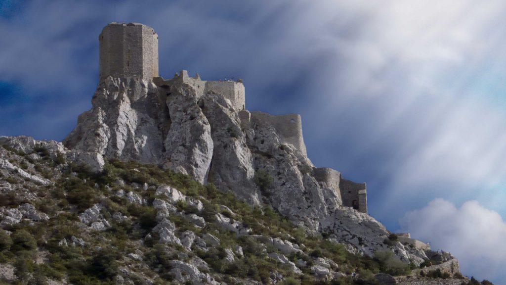 Borg højt oppe på en klippe. Solstråler skinner på borgen