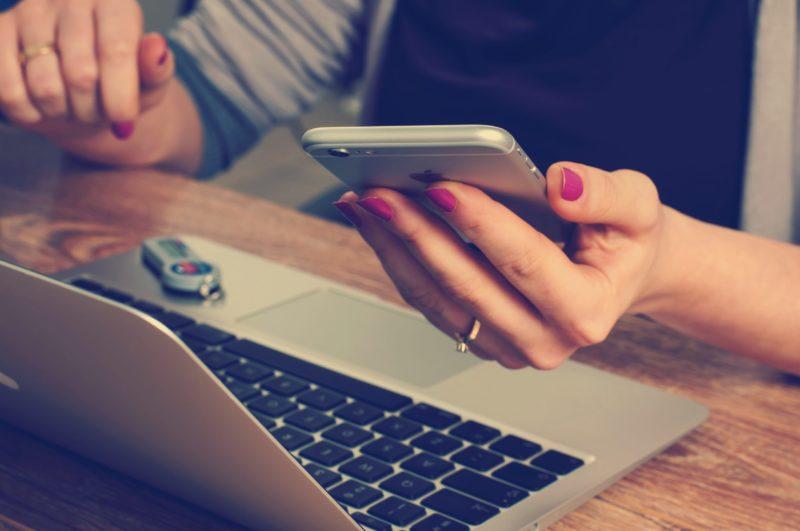 Kvinna som sitter med dator och telefon